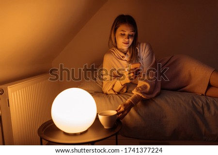 Young woman laying in bed, drinking tea and using her mobile phone before sleeping Stock foto ©