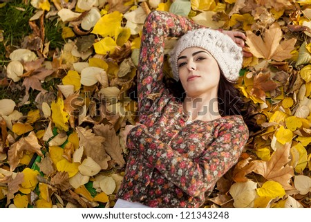 Young woman laying in the autumn leaves