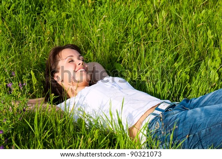 Young woman laying on a lawn or meadow in summer and is dreaming or sleeping