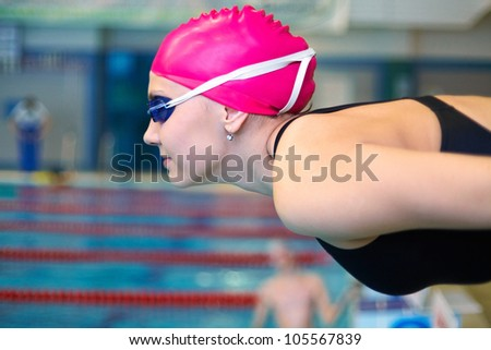 young woman leaning at the start before the swimming pool