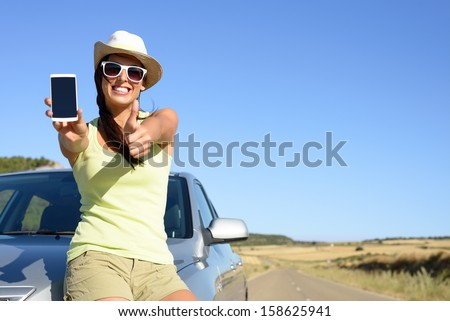 Young woman leaning on car showing cell phone screen and doing thumbs up gesture. Positive woman giving her approval to car insurance service.