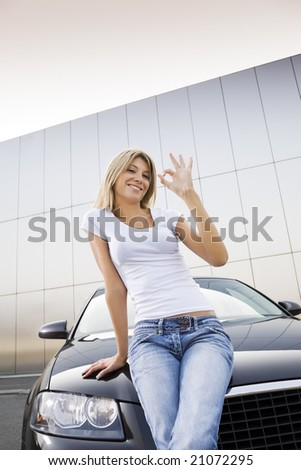 Young woman leaning on new car and similing