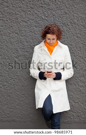 Young woman leaning on wall looking at her cell phone