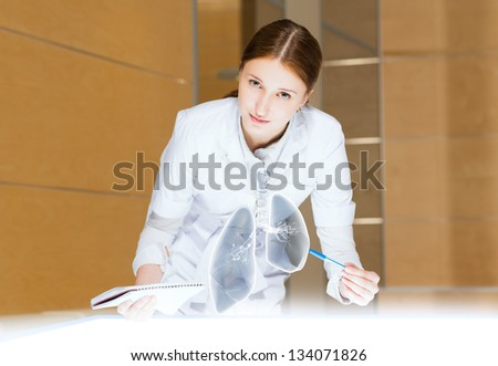 young woman leaning over a medical researcher illuminated table, the concept of modern technology in medicine
