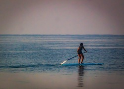 Young woman learning how to paddleboard in the beach in Goa enjoying water sports