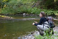Young woman learning to fly fishing with a profesional guide