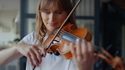 Young woman learning to play violin at home. Romantic girl playing violin with bow. Portrait of female musician performing on string instrument. Dreamy violinist fingers pressing strings on violin
