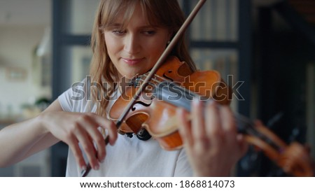 Young woman learning to play violin at home. Romantic girl playing violin with bow. Portrait of female musician performing on string instrument. Dreamy violinist fingers pressing strings on violin Сток-фото ©