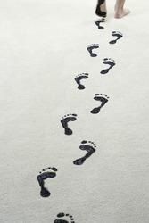 Young woman leaving black footprints on carpet