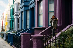 Young woman leaving her house and using her smart mobile with colorful houses on Portobello Street in the Notting Hill neighborhood