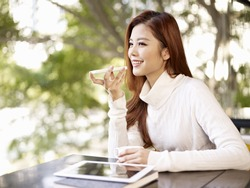 young woman leaving voice message using mobile phone.