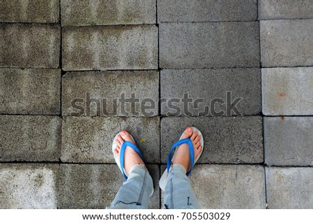 ac044a90340d Young Woman legs in Blue Sandals and Blue Jeans. Female Standing on The  Cement Background