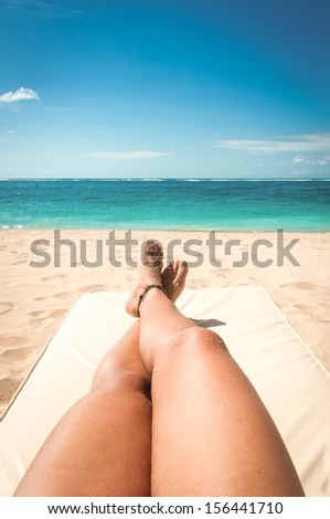 Young woman legs sunbathing on the beach