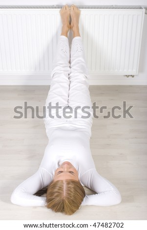 Young woman lie on floor near radiator