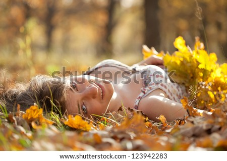 Young woman lies in oak leaves at autumn park