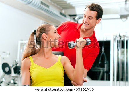 Young woman lifting a dumbbell in the gym assisted by her personal trainer (focus on woman)