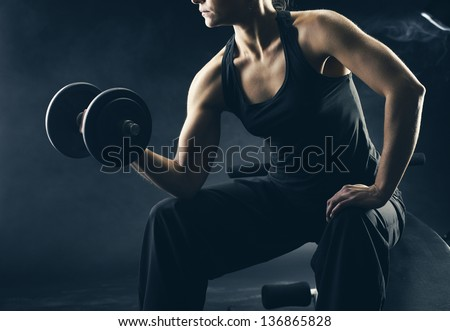 Young woman lifting the dumbbells