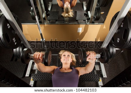 Young Woman Lifting Weights in Fitness Center