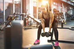 Young woman lifting weights in gym.