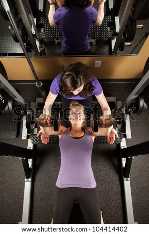 Young Woman Lifting Weights with Personal Trainer