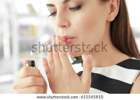 Young woman lighting cigarette at home #615545810  sc 1 st  Avopix.com & Free Young beautiful woman lights a cigarette with lighter Photos ... azcodes.com