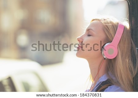 young woman listening music in...