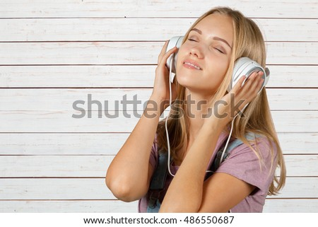 young woman listening music with headphones #486550687