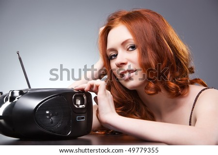 Young woman listening radio. On gray wall background. - stock photo