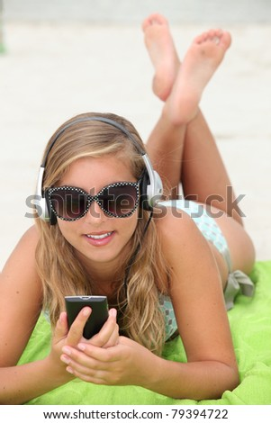 Young woman listening to music while tanning at the beach