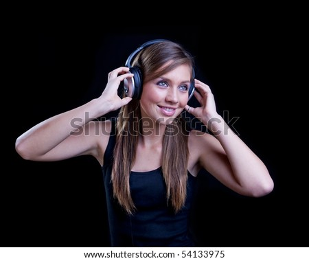 Young woman listening to music with headphones on black background.