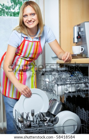 young woman loading dishes to the dishwasher