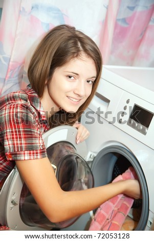 Young woman loading the washing machine in bathroom