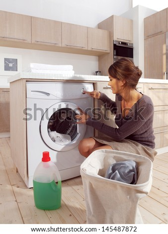 Young woman loading the washing machine in room