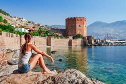 Young woman look at Kizil Kule tower in Alanya peninsula, Antalya district, Turkey, Asia. Famous tourist destination with high mountains. Part of ancient old Castle. Summer bright day