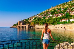 Young woman look on ancient shipyard from Kizil Kule tower in Alanya peninsula, Antalya district, Turkey, Asia. Famous tourist destination with high mountains. Part of ancient old Castle. Summer day