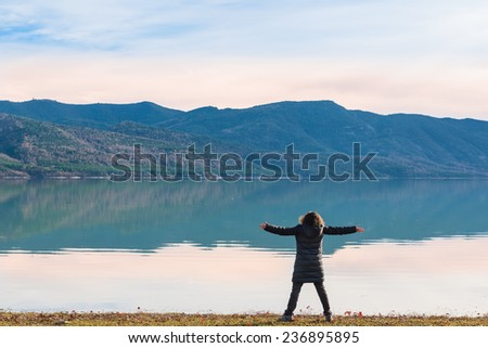 Young woman looking at a lakeside winter landscape