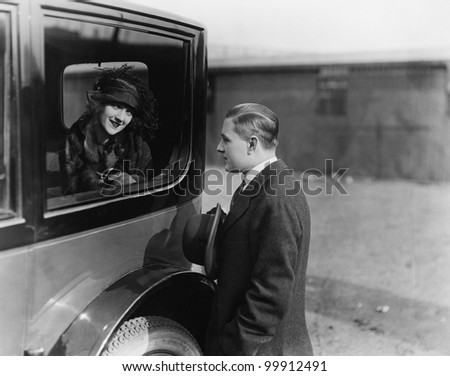Young woman looking at a man through a car window
