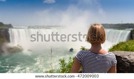 Young woman looking at amazing Niagara falls. Canada Ontario