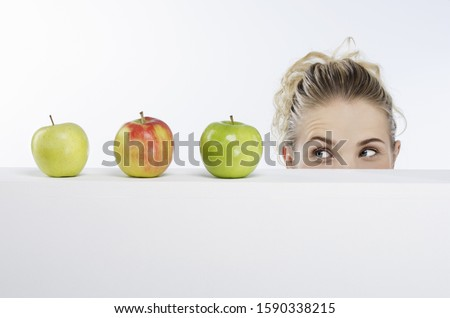 Young woman looking at apples