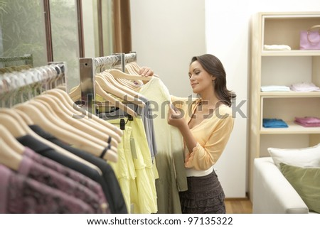 Young woman looking at clothes in fashion clothes.