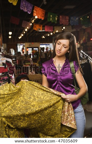 Young woman looking at colorful clothing while shopping. Vertical shot.