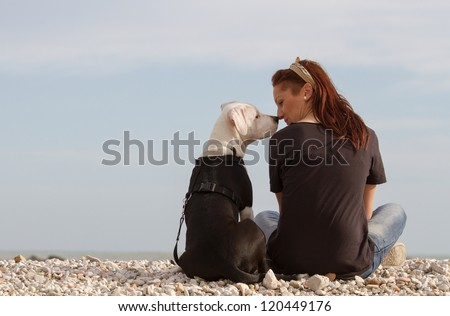Young woman looking at dog nose to nose