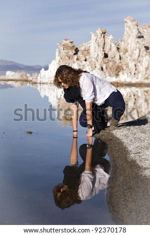 Young woman looking at her reflection at Mono Lake, California!