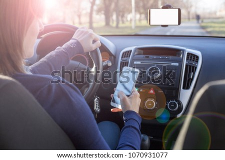 Young woman looking at her smartphone and texting message while driving a car. Distracted driver. Smartphone in a car use for Navigate or GPS. Mobile phone with white screen. Dangerous driver.