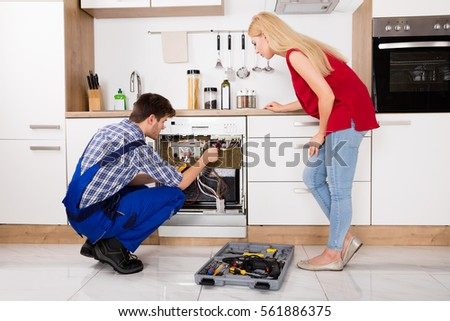 Young Woman Looking At Male Technician Checking Dishwasher With Digital Multimeter In Kitchen #561886375