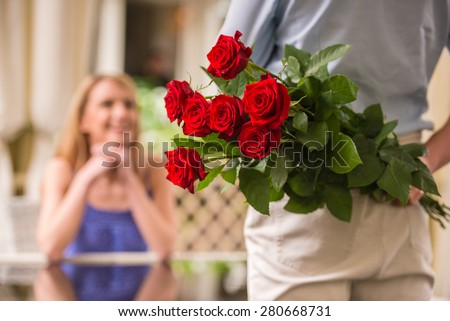 Young woman looking at man with flower bouquet behind the back.