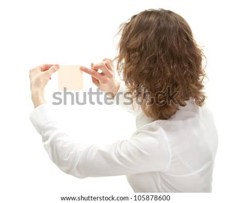 Young woman looking at paper note pointing at it, rear view, isolated on white