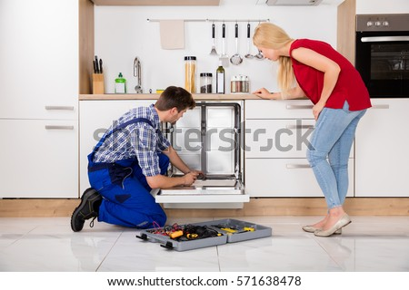 Young Woman Looking At Repairman Repairing Dishwasher In Kitchen #571638478
