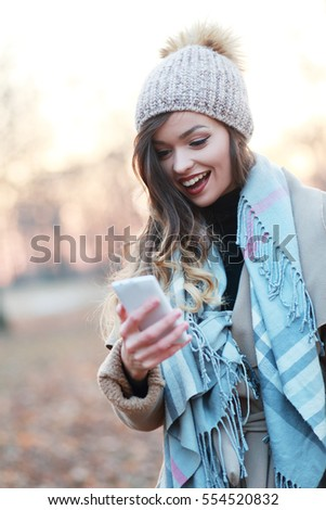 young woman looking at smart phone with a big smile, good news