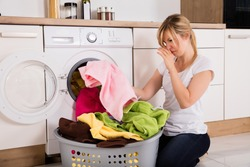 Young Woman Looking At Smelly Clothes Out Of Washing Machine In Kitchen